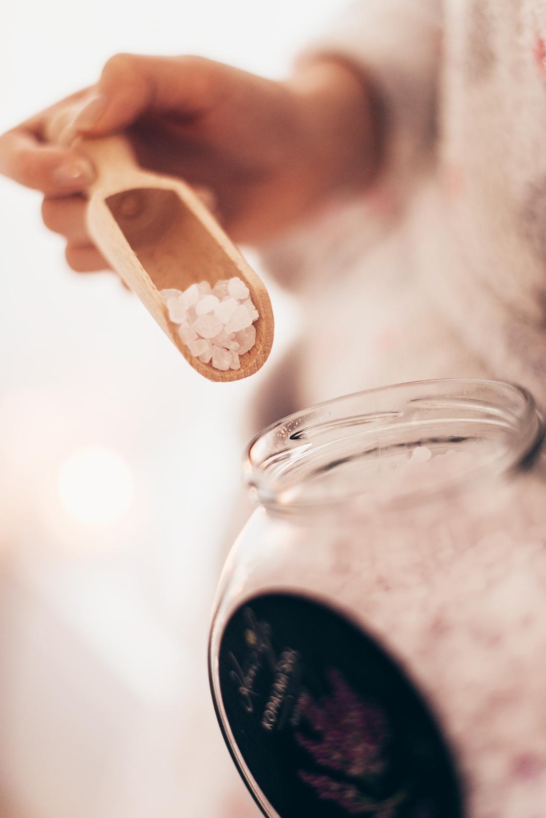 V lepo oblikovan steklen kozarec kopalne soli je vstavljena tudi lesena žlička za posipanje kopalne soli.